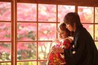 紅葉のきれいな季節に和室の縁側で和装の婚礼前撮りをする赤い色打掛を着た新婦と新郎