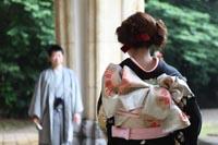旧前田侯爵邸の車止めで和装の婚礼前撮り写真を撮るグレーの紋付き袴の新郎と黒引き振袖を着た新婦の後ろ姿