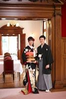 旧古河庭園洋館の自然光の入る明るい喫茶スペースで和装の新郎と黒引き振袖を着た新婦のフォーマルなフォトウェディング写真