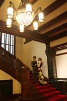 旧前田侯爵邸の豪華なシャンデリアと階段でフォーマルな雰囲気で婚礼の前撮り写真を撮る洋装の新郎と和装の新婦
