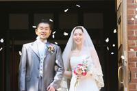 チャペルで挙式を挙げたタキシードの新郎とウェディングドレスの新婦に、フラワーシャワーで祝福をする写真