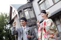 旧細川侯爵邸の中庭でシャボン玉を吹いて遊ぶグレーのタキシードを着た新郎と緑の色打掛を着た新婦の和装と洋装の婚礼前撮り写真