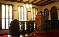 旧前田侯爵邸で輝くシャンデリアとステンドグラスを見つめる洋装の新郎と色打掛を着た新婦のドラマチックな後ろ姿を写したウェディングフォト
