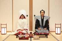 畳の上で日本食のお膳を前に正座をする裃月代の武士風の衣装を着た新郎と綿帽子に白無垢姿の新婦の江戸時代風の和装の婚礼前撮り写真