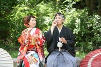 東京の新緑がきれいな日本庭園で、和傘とシャボン玉を小道具に、カジュアルな和装前撮りを撮る新郎と赤い色打掛を着た新婦