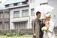 旧細川侯爵邸の中庭で日傘をさすフロックコート姿の新郎と白無垢姿の新婦の和装と洋装の婚礼前撮り写真