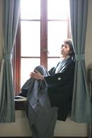 旧前田侯爵邸の自然光が入る明るい居室の窓辺でクールカジュアルなポーズをとる和装の新郎のドラマチックなウェディングフォト