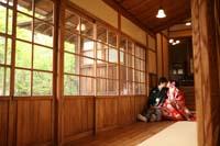 ガラス障子のあるお茶室の縁側で内緒話をする新郎と赤い色打掛の新婦の和装の婚礼前撮り写真
