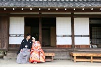 東京のお茶室がある日本庭園で、仲良くくつろぐ新郎と赤い色打掛を着た新婦の和装前撮り