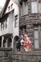 旧細川侯爵邸の石造りのバルコニーで仲良く並ぶ新郎と赤い色打掛の新婦の和装の婚礼前撮り写真