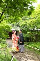 新緑がきれいな庭園で和装の婚礼前撮り写真を撮る新郎と生花ブーケを持つ赤い色打掛の新婦