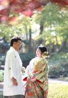東京の紅葉がきれいな日本庭園で、自然光の中、カジュアルな雰囲気で和装の前撮りをする、白の紋付き袴姿の新郎と緑色の打掛を着た新婦
