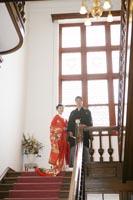 旧古河庭園洋館の、ステンドグラスが見える階段で、フォーマルな雰囲気の和装前撮り写真を撮る新郎と赤い色打掛の新婦