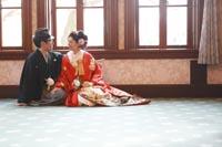 旧前田侯爵邸の自然光が入る明るい居室で仲良く寄り添う和装の新郎と赤い色打掛の新婦のモダンカジュアルなウェディングフォト
