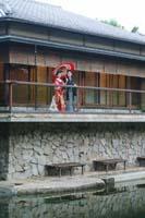 池を石垣の上にあるお茶室から眺める赤い和傘を持つ新郎と赤い色打掛の新婦の和装婚礼前撮り写真