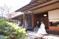 お茶室の縁側に座り、日本庭園の中庭を眺める新郎と白無垢姿の新婦の和装の婚礼前撮り写真