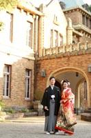 旧前田侯爵邸の車止めで輝く外観を背景に婚礼前撮り写真を撮る和装の新郎と赤い色打掛の新婦