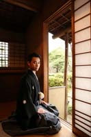お茶室から正座をしながら庭園を眺める黒紋付きの新郎の和装婚礼前撮り写真
