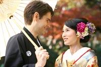 東京の紅葉がきれいな日本庭園で、秋に和装の婚礼前撮りをする和傘を持つ新郎と緑の色打掛を着た新婦