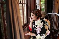 旧前田侯爵邸の自然光が入る窓辺に座り外を眺めるモダンな雰囲気の黒引き振袖を着た新婦の和装婚礼前撮り写真
