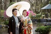 池ののある日本庭園で白い和傘を持つ新郎と緑色の色打掛をの新婦の和装婚礼前撮り写真