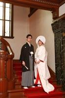 旧前田侯爵邸の赤絨毯の階段で並んで和装の婚礼前撮り写真を撮る紋付き袴の新郎と綿帽子に白無垢姿の新婦