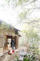 日本庭園のあるお茶室の縁側に座る新郎と色打掛の新婦の和装の前撮り婚礼写真