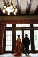 旧前田侯爵邸の自然光が入る明るい居室で並んで写る後ろ姿の和装の新郎と赤い色打掛の新婦の婚礼前撮り写真