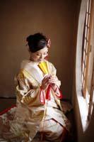 丸い窓、悟りの窓の前で金色の扇子を持つ白と金刺繍の打掛を着る正座した新婦