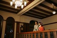 旧前田侯爵邸で和装の婚礼前撮り写真を撮るグレーの紋付き袴を着た新郎と赤い色打掛の新婦の写真