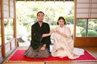 畳のある和室の縁側に赤い敷物を敷いて和装の婚礼前撮り写真を撮る新郎と白無垢姿の新婦