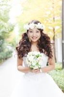 イチョウの美しいシーズンに並木道でウェディングドレスを着てフォトウェディング