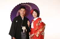 東京の撮影スタジオで赤い色打掛と紋服の和装支度でフォトウェディングをする新郎新婦