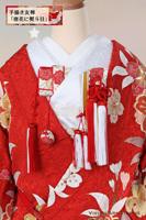 長寿の意味もある熨斗目文様に唐花を散りばめた手描き友禅の色打掛に、赤の小花柄が入った筥迫や懐剣の小物を合わせて