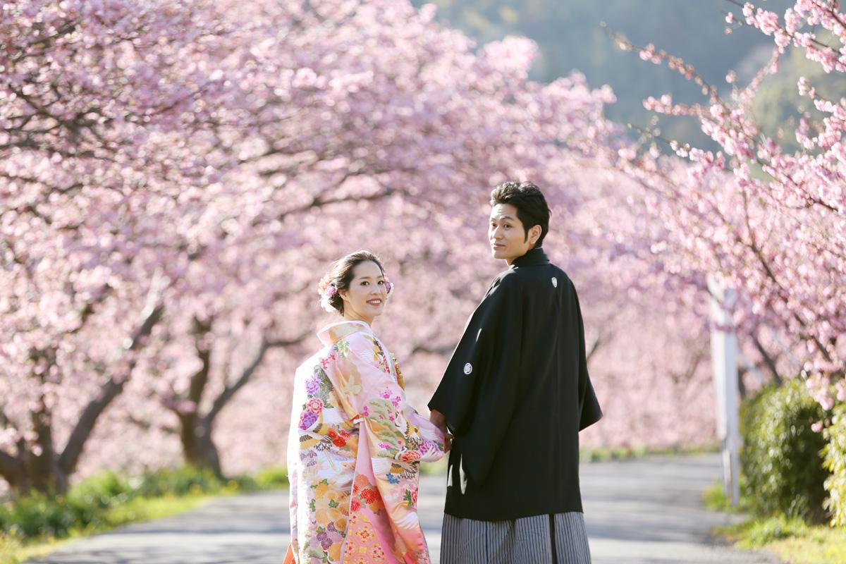 桜のトンネルでポーズをとる新郎新婦