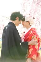 桜の木の下で新婦様を抱き寄せる新郎様