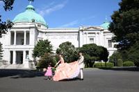 サーモンピンクのカラードレスを着た新婦様と表慶館の前で楽しく撮影