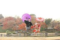 木々が紅葉した日本庭園で元気にジャンプする新郎新婦様