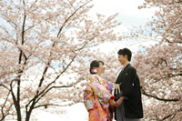 満開の桜を背景に笑顔の新郎新婦様