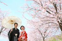 桜の下で満面の笑みを浮かべる新婦様と新郎様